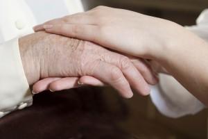 Een verpleegster houdt de handen vast van een oudere vrouw.