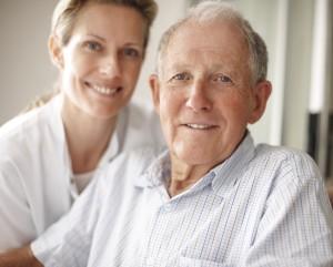 Een foto van een tevreden bejaarde man in een rolstoel, met een zuster ter assistentie.